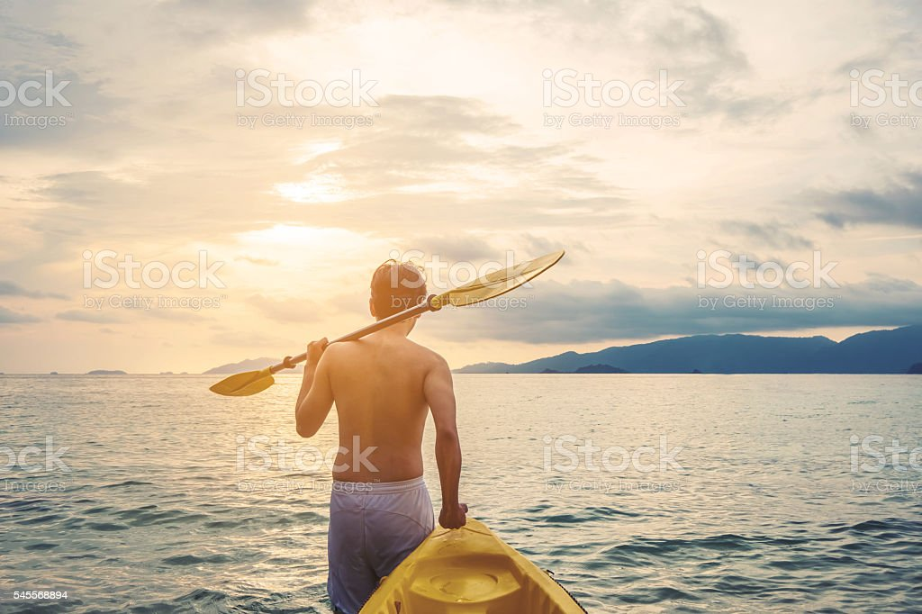 Asian guy pulling kayak to sea in sunset, vintage tone stock photo