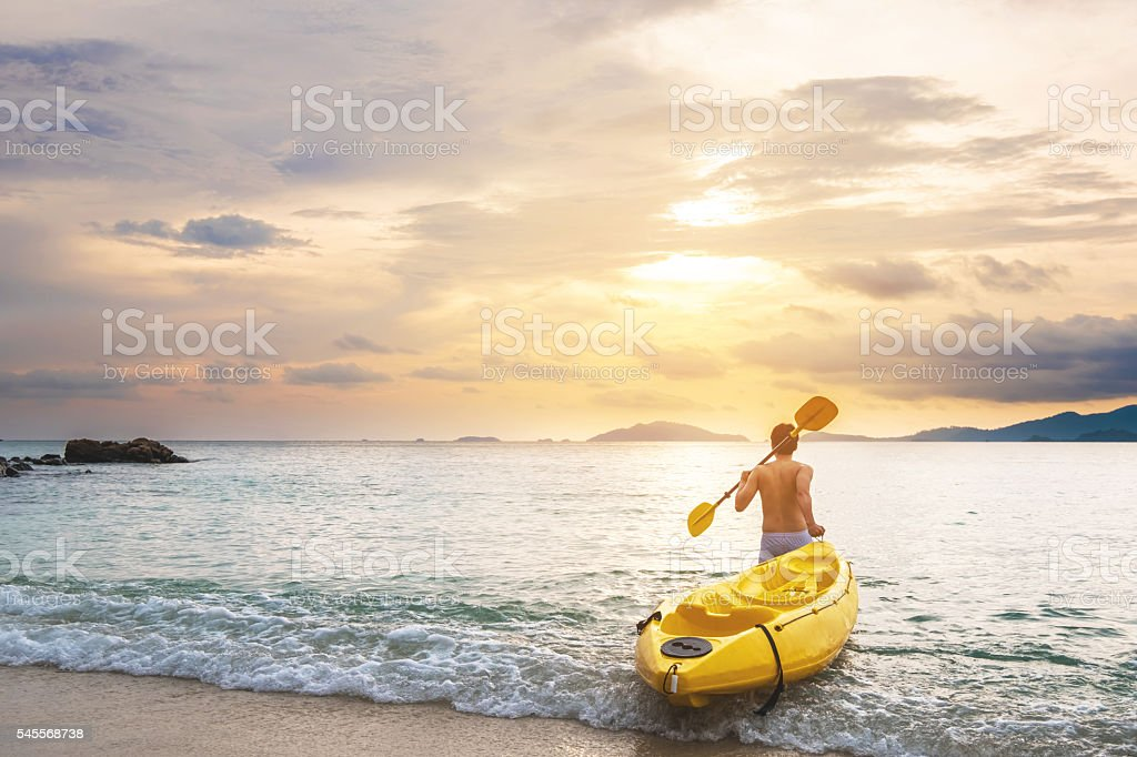 Asian guy pulling kayak to the sea in sunset stock photo