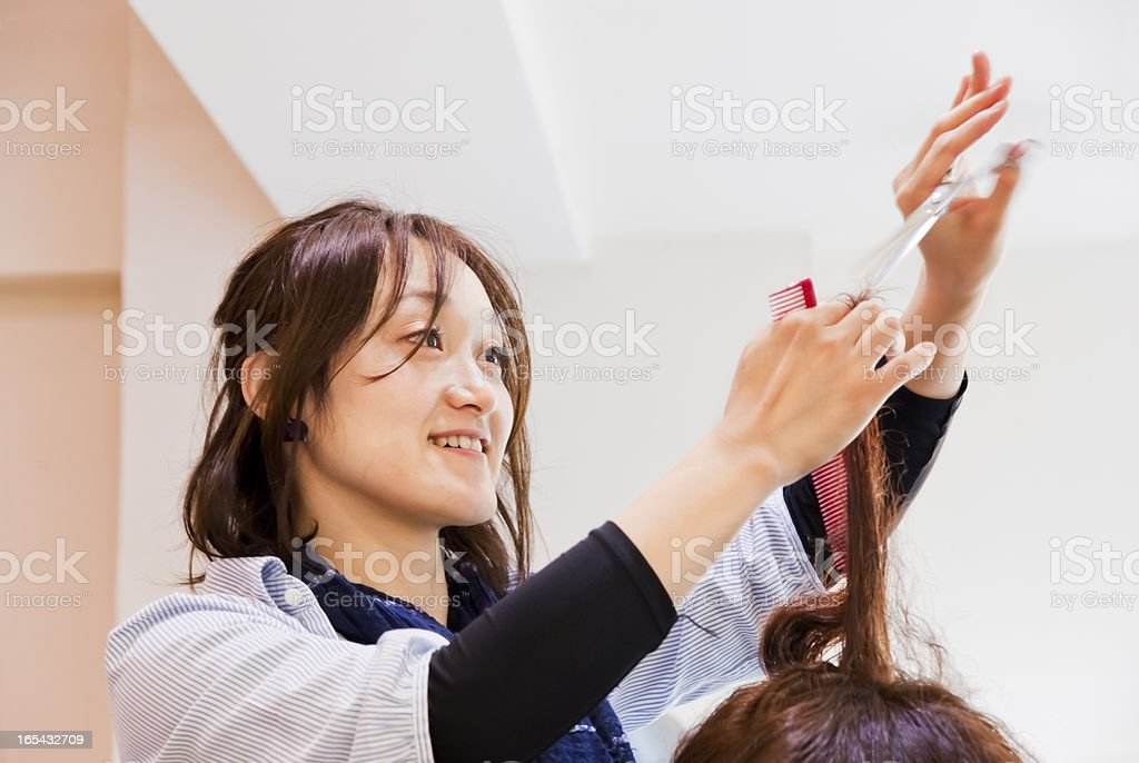 Asian hairdresser, cutting hair stock photo