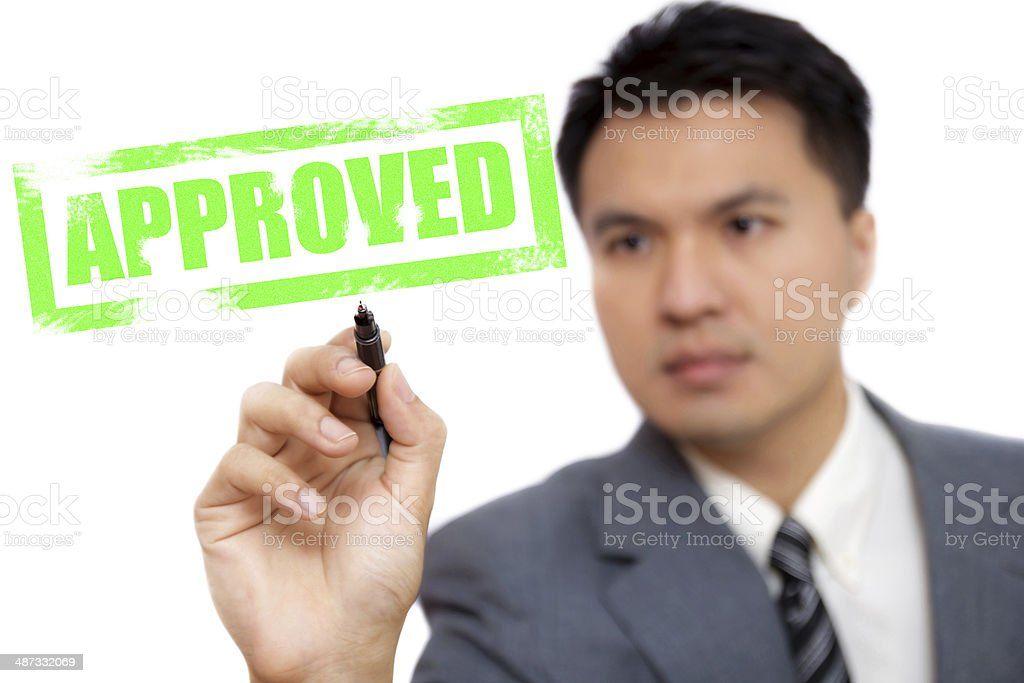 Asian handsome businessman write 'APPROVED' royalty-free stock photo