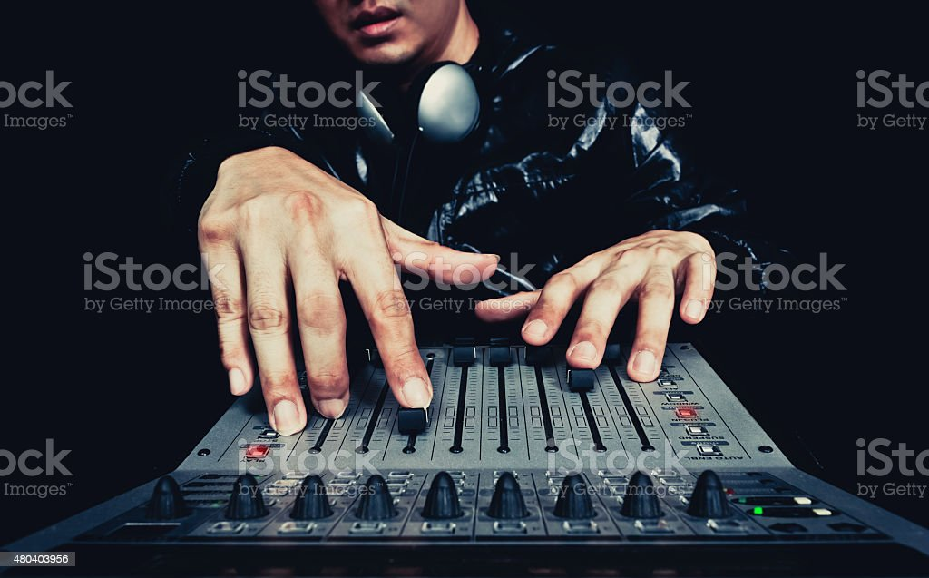asian handsome DJ, producer working on digital studio mixer stock photo
