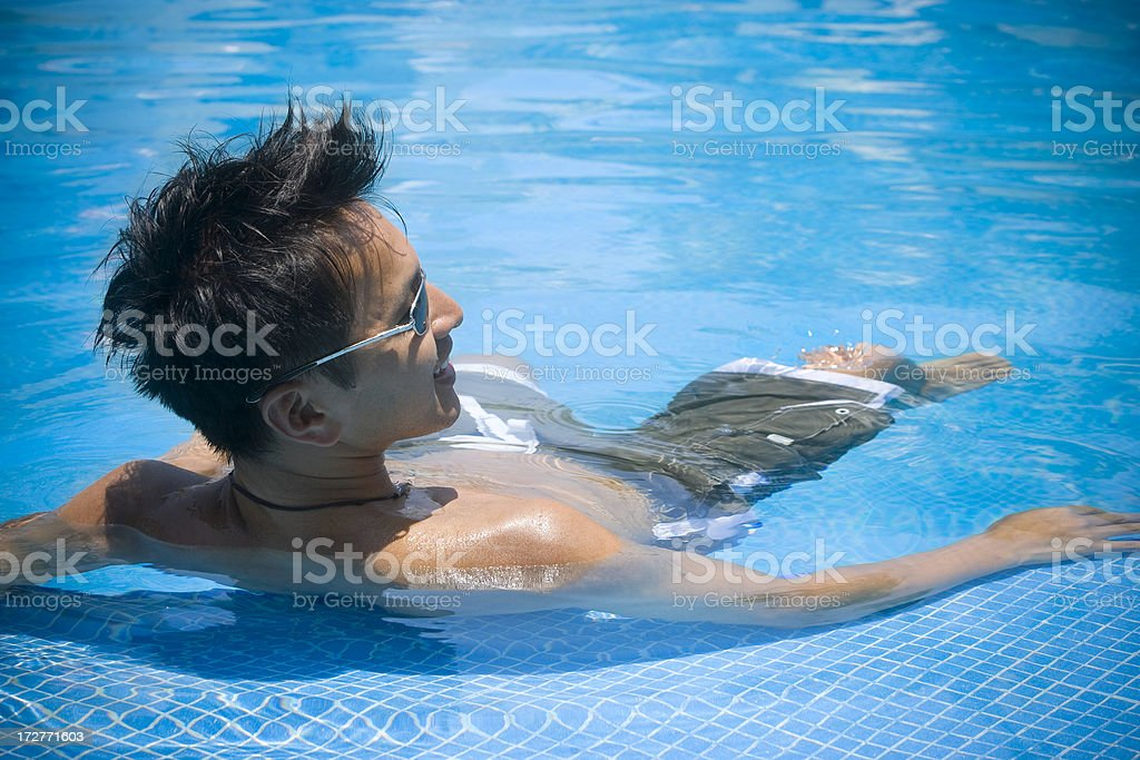Asian Handsome Young Man Floating on Back, Blue Pool, Copyspace royalty-free stock photo