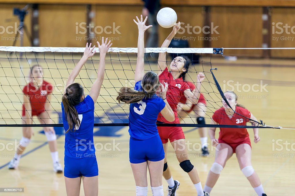 Asian high school volleyball player spikes volleyball against female opponents stock photo