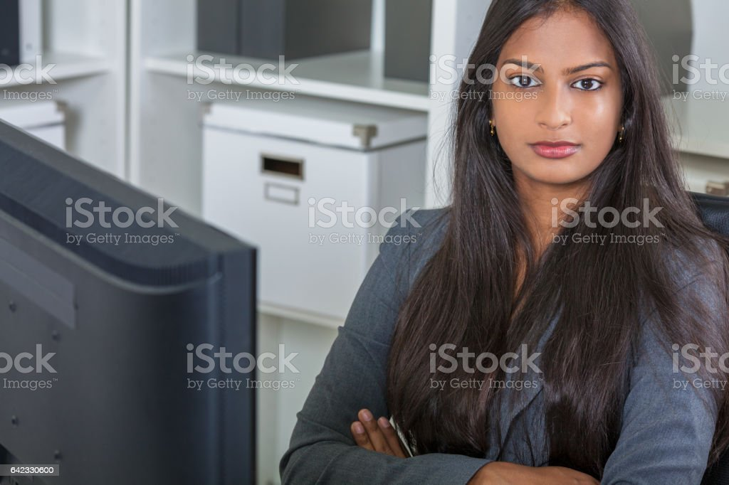 Asian Indian woman or businesswoman in office sitting at a desk arms folded with a computer stock photo