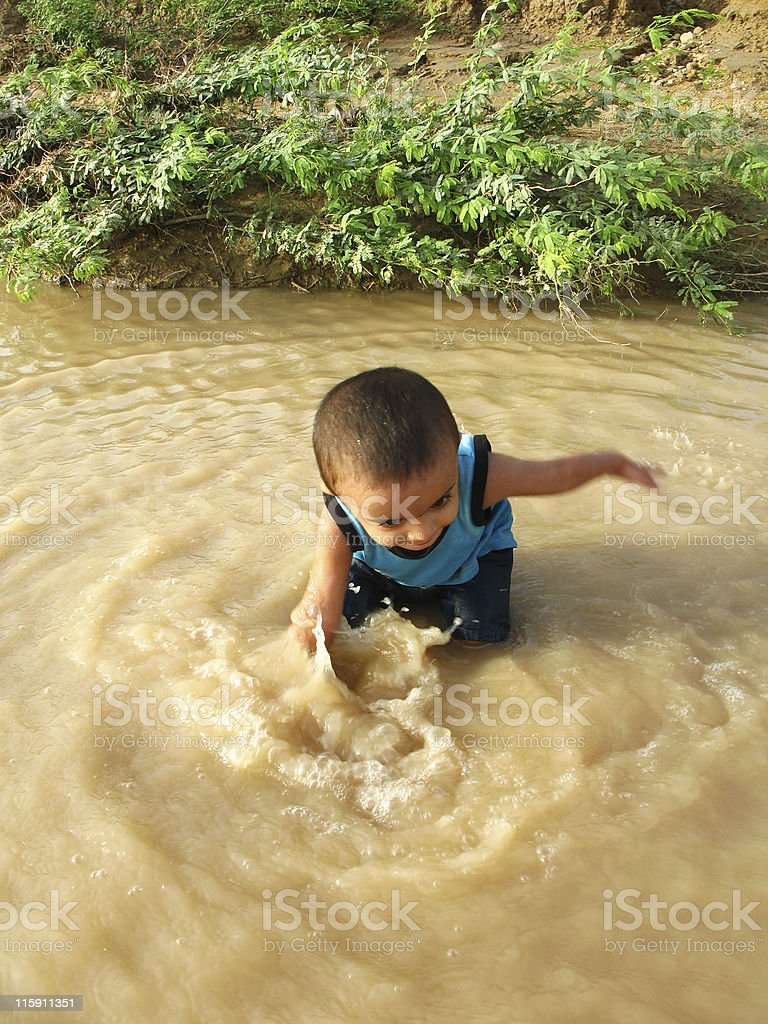 Asian kid playing in stream of water royalty-free stock photo