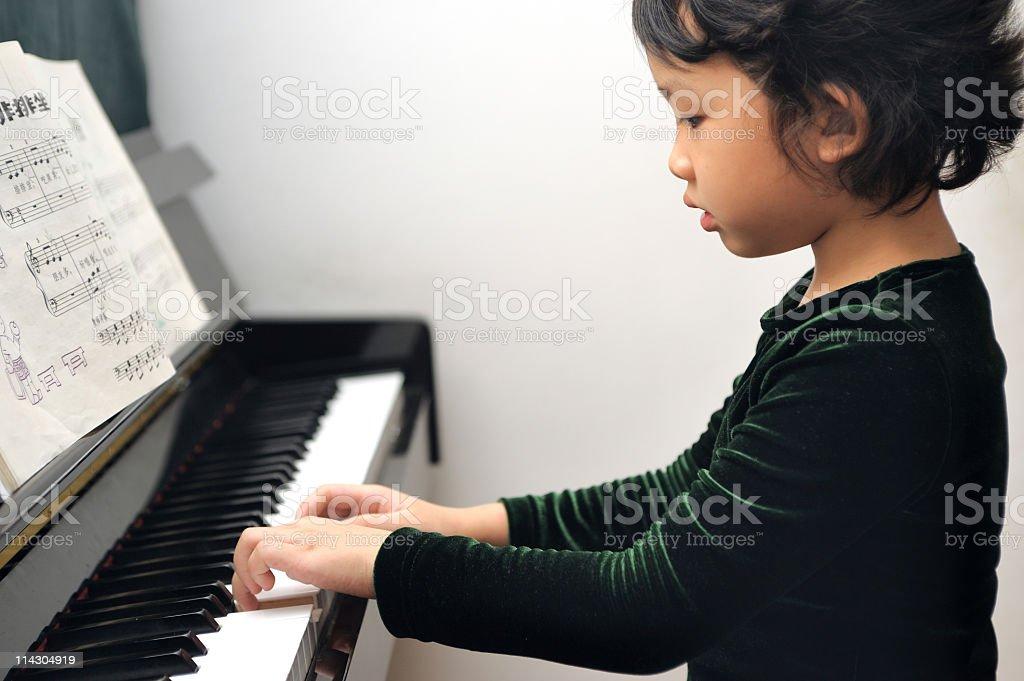 Asian kid playing piano royalty-free stock photo