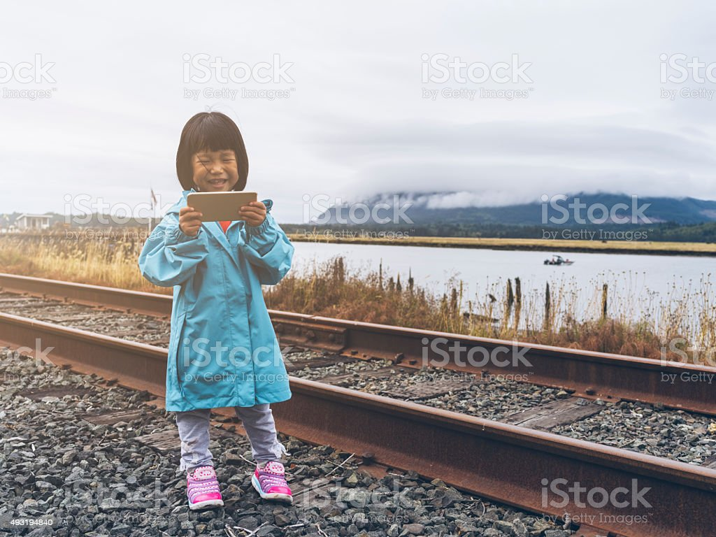 asian kid standing aside river using cellphone stock photo