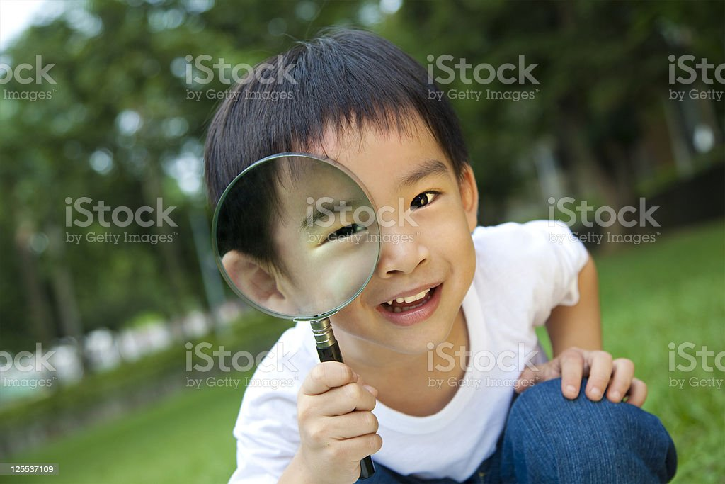 asian  kid with magnifying glass stock photo