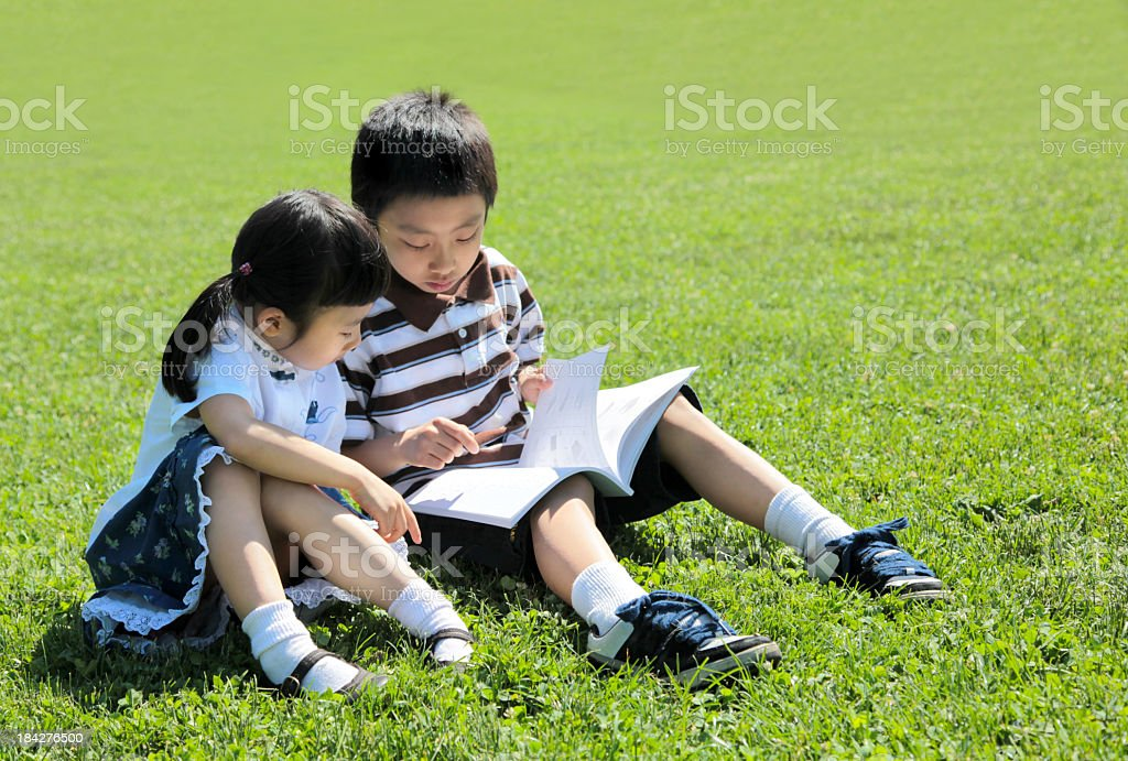 Asian Kids Reading Book in A Park royalty-free stock photo