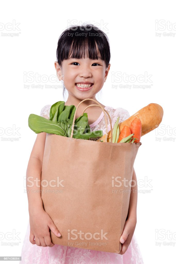 Asian little chinese girl carrying shopping bag with groceries stock photo