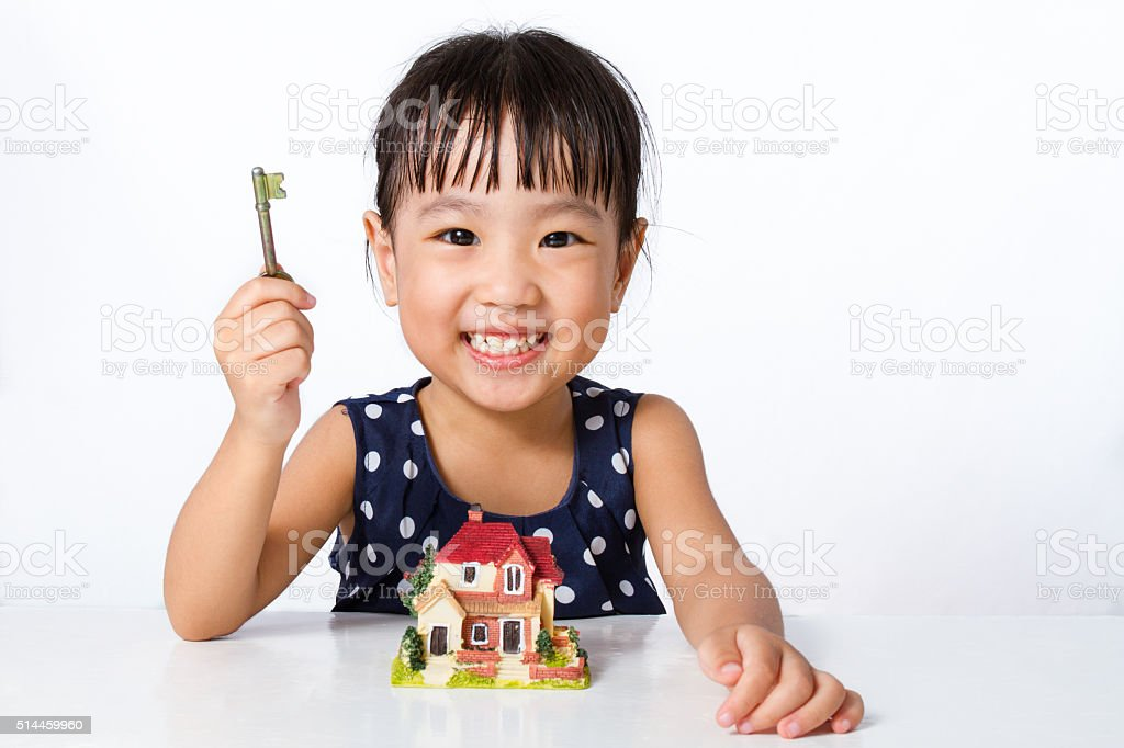 Asian Little Chinese Girl Holding Key for Property Concept stock photo