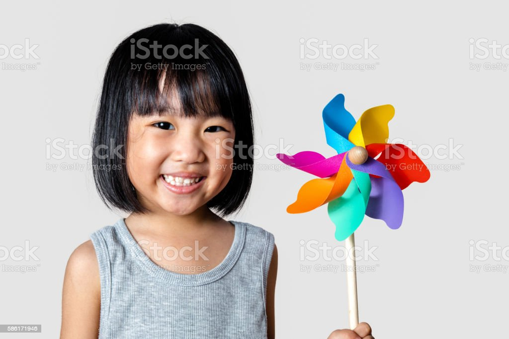 Asian Little Chinese Girl Playing Colorful Pinwheel stock photo