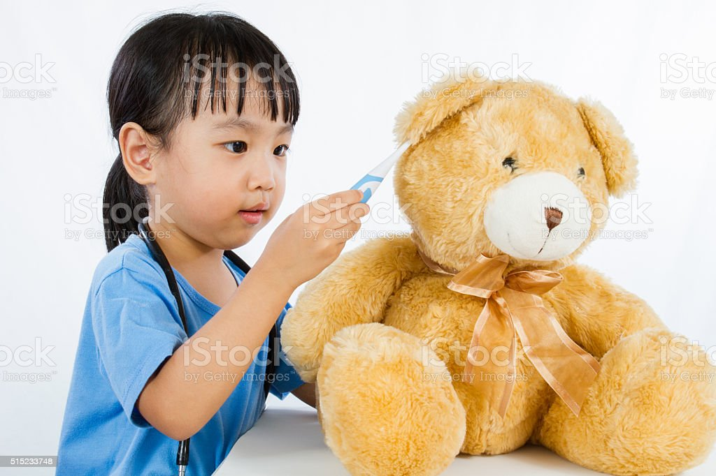 Asian Little Chinese Girl Playing Doctor with Teddy Bear stock photo