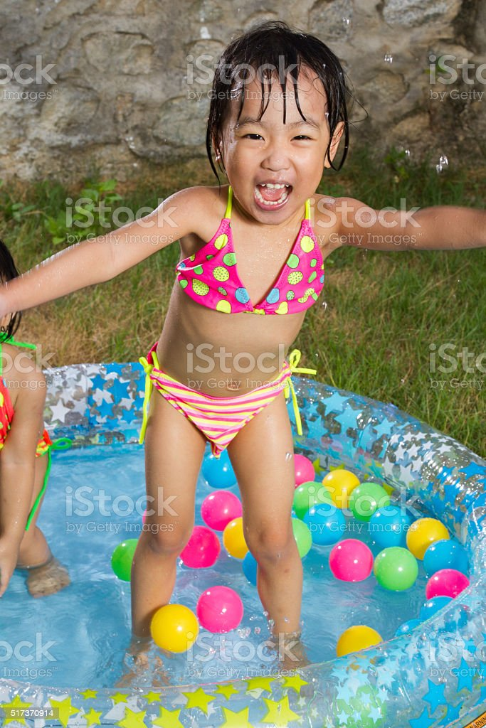 Asian Little Chinese Girl Playing in an Inflatable Rubber Swimmi stock photo