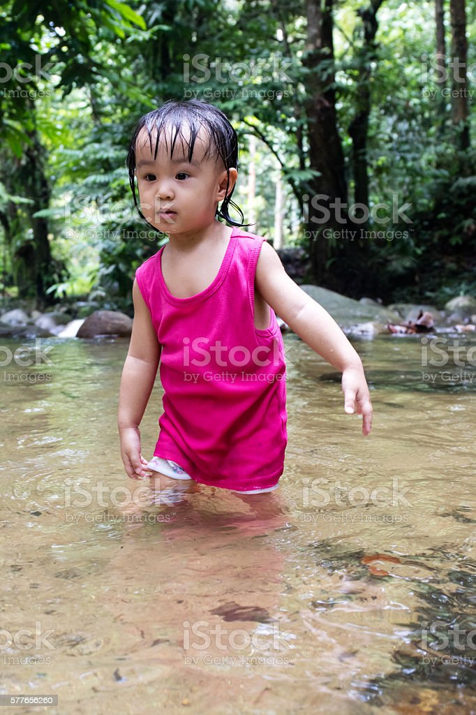 Asian Little Chinese Girl Playing in Creek stock photo