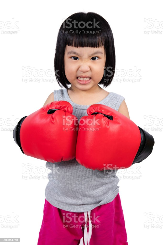 Asian Little Chinese Girl Wearing Boxing Glove With Fierce Expre stock photo