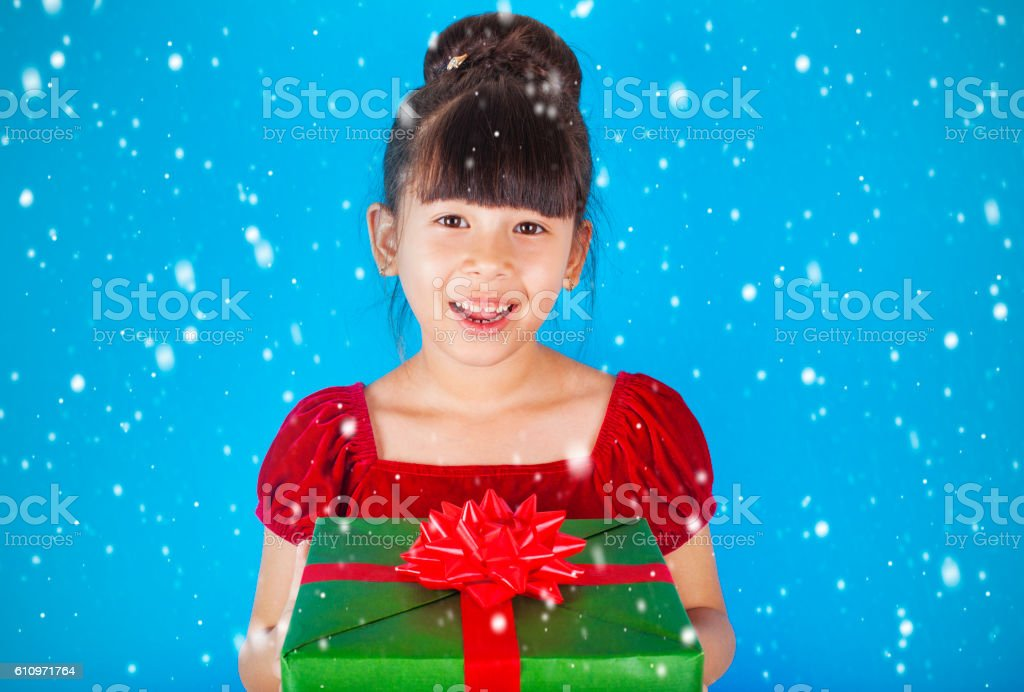 Asian little girl holding big Christmas gift box. stock photo