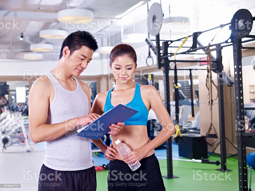 Asian male and female in gym looking at clipboard stock photo