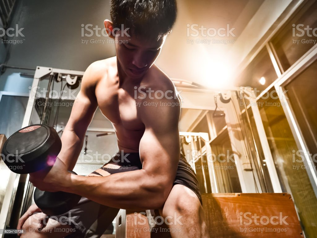 Asian male bodybuilder athlete with dumbbell, show biceps, triceps muscles and perfect fit upper body and torso at gym stock photo