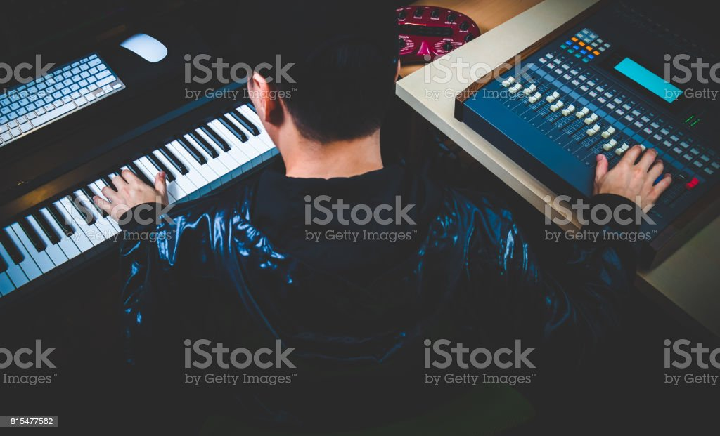 asian male music composer making songs in digital recording studio