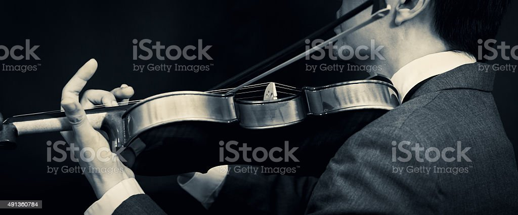 Asian male musician playing violin on dark background stock photo