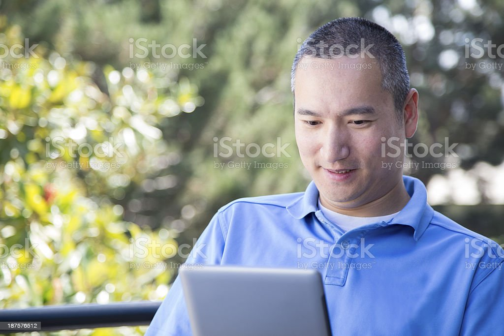 Asian Male on His Ipad royalty-free stock photo