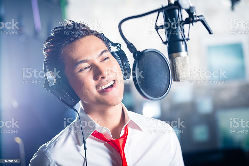 Asian male singer producing song in recording studio stock photo