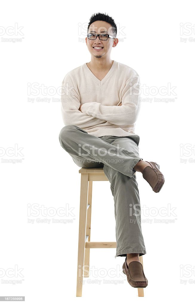 Asian male sitting on a chair stock photo