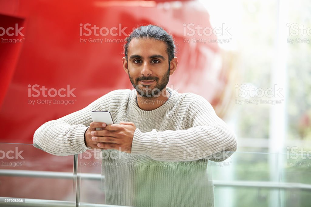 Asian male university student holding smartphone, portrait stock photo