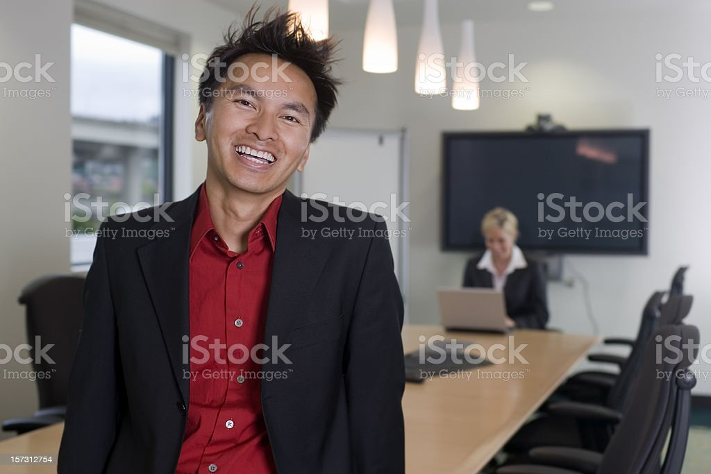Asian Man and Caucasian Woman Business Team in Meeting Room royalty-free stock photo