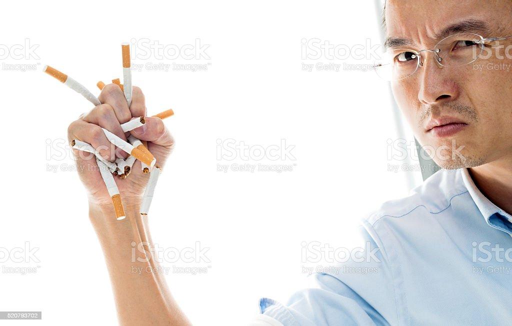 Asian man crushing cigarettes stock photo