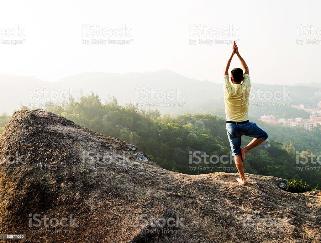 Asian man doing yoga on mountain peak stock photo