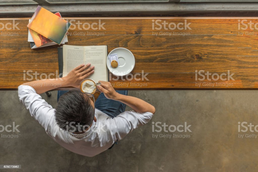 Asian man enjoying a beautiful day with book and coffee stock photo