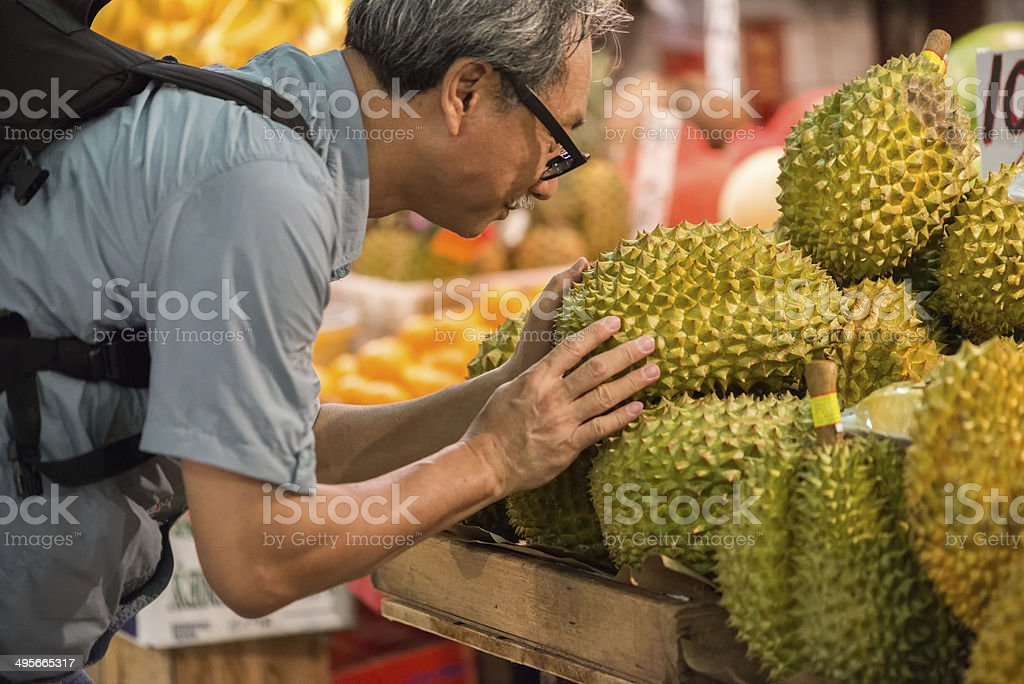 Asian Man Examining Durian Fruit at a Market stock photo