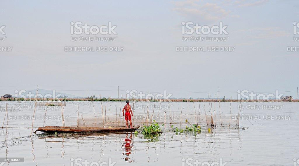 Asian man fishing on lake in Vietnam stock photo