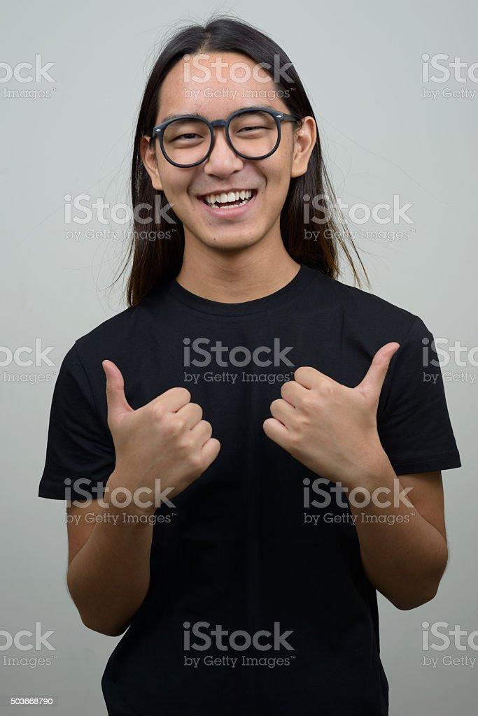 Asian man giving thumbs up stock photo