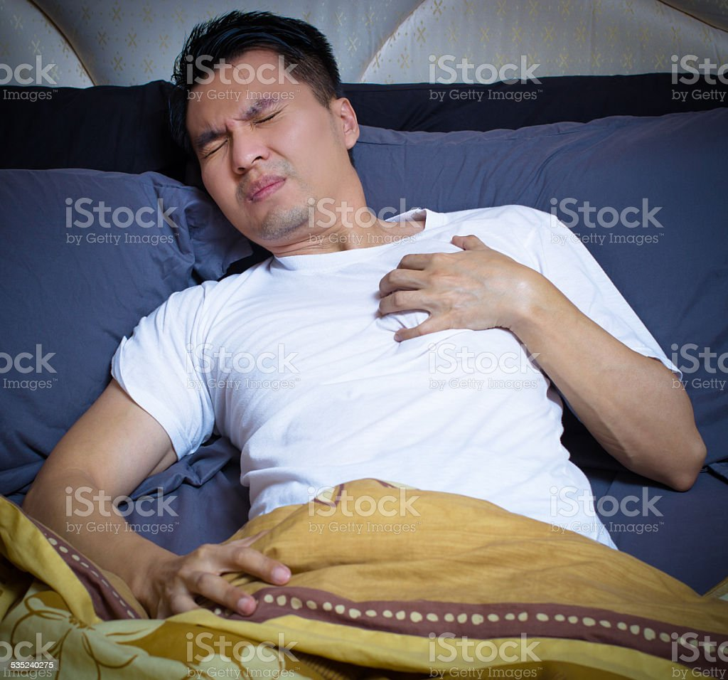 asian man has a heart attack symptoms on bed stock photo