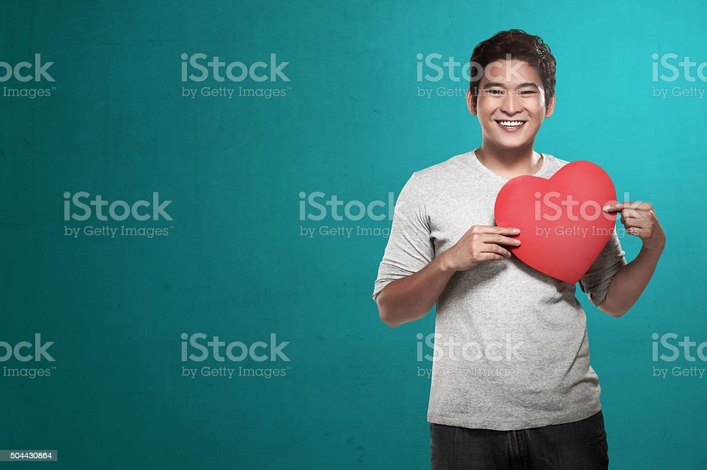 Asian man holding red heart stock photo