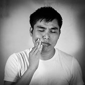 Asian man in a white t-shirt has a toothache