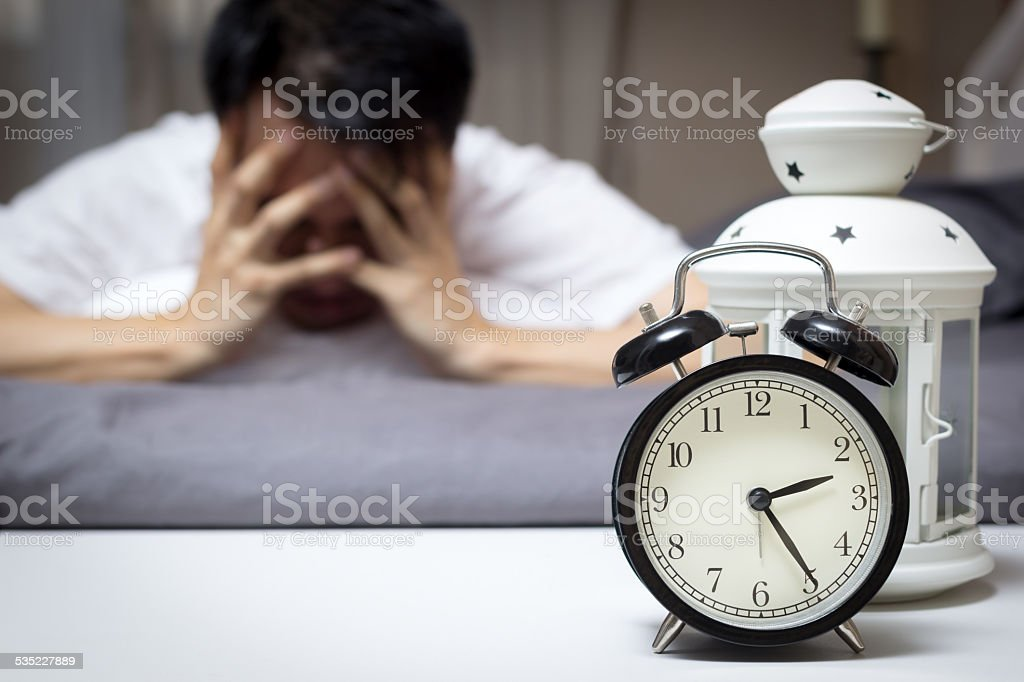 Asian man in bed suffering insomnia and sleep disorder stock photo