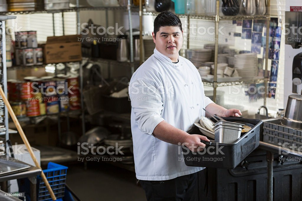 Asian man in restaurant carrying tub of dirty dishes stock photo