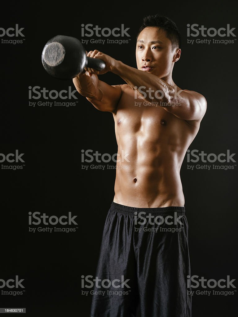 Asian man lifting a kettle bell royalty-free stock photo