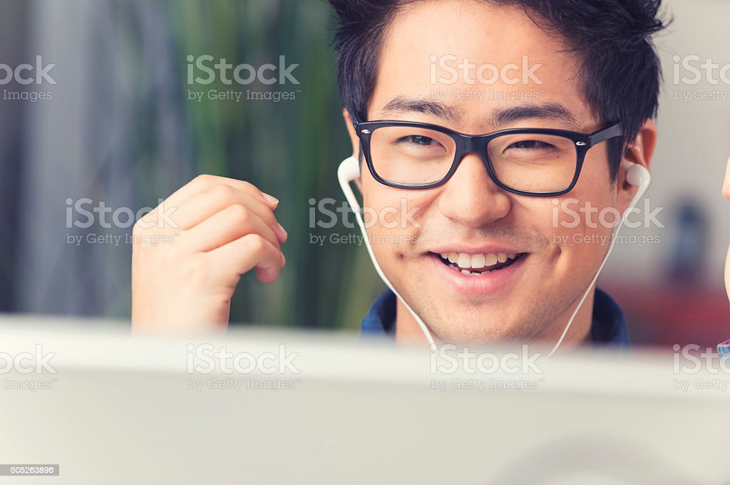 Asian man listening to music with headphones stock photo