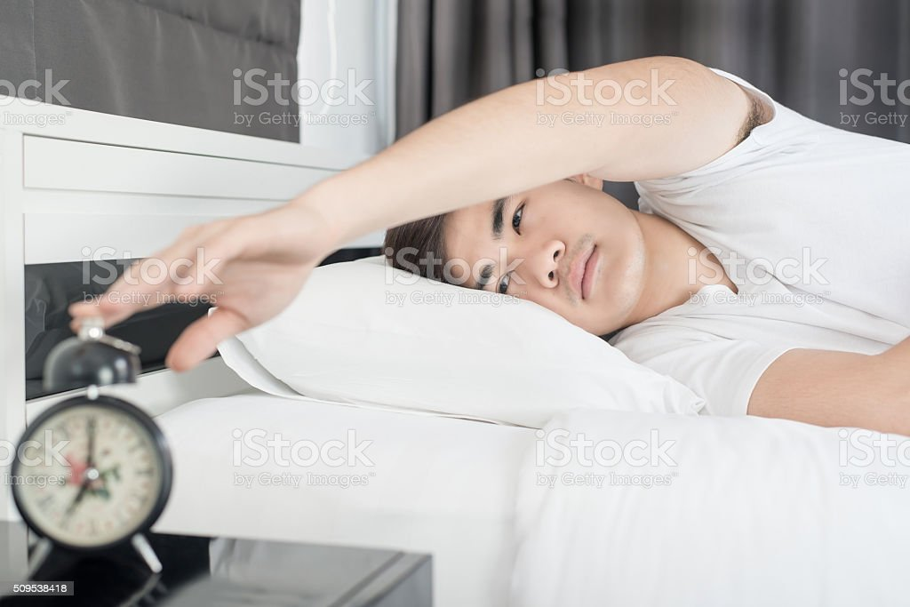 Asian man lying on the bed and stopping alarm clock stock photo