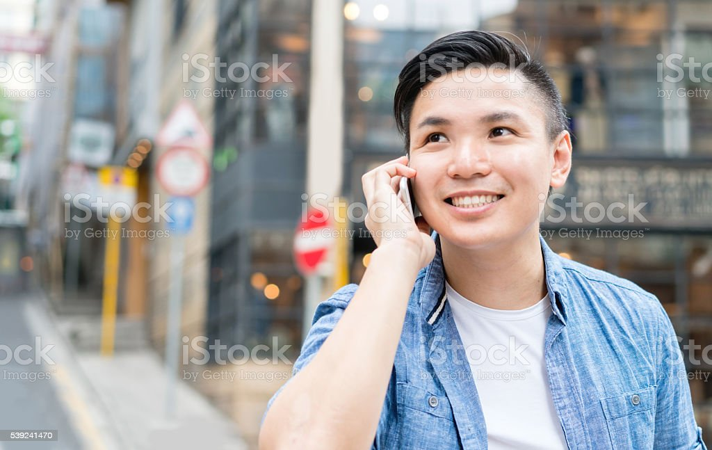 Asian man outdoors on the phone stock photo