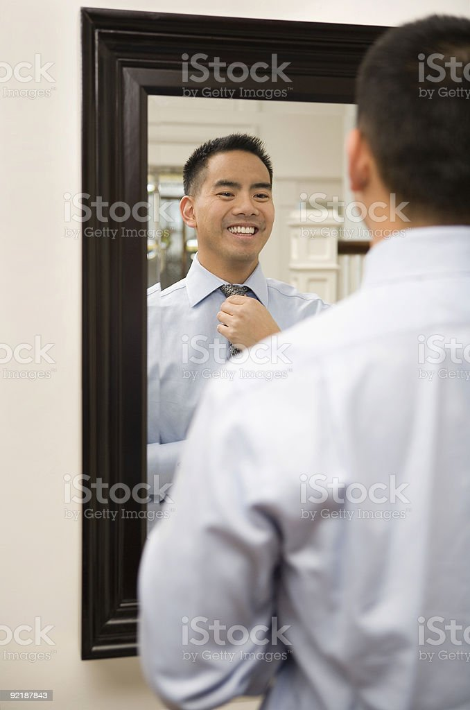 asian man putting on tie in front of mirror royalty-free stock photo