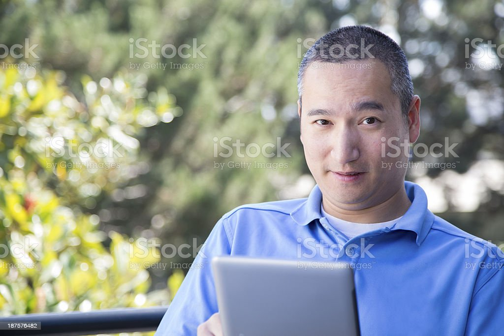 Asian Man Reading Book on Tablet royalty-free stock photo