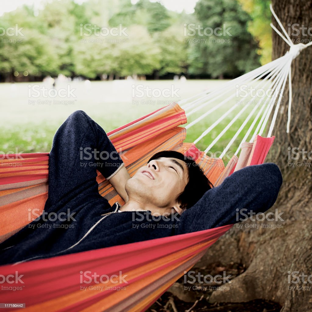 Asian Man Relaxing in a Hammock royalty-free stock photo
