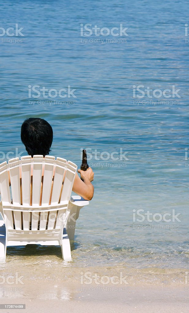 Asian Man Sitting in Caribbean Sea Beach Chair Holding Beer royalty-free stock photo