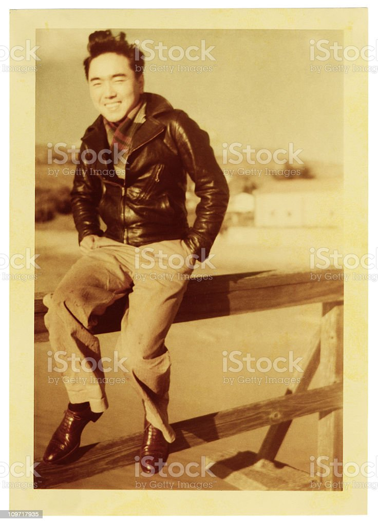 Asian Man Sitting on a Railing stock photo